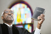African American Reverend holding up Bible — Stock Photo