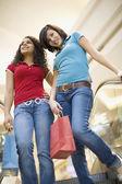 Multi-ethnic teenage girls riding escalator in mall — Stock Photo