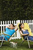 Multi-ethnic couple relaxing in lawn chairs — Foto de Stock