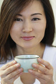 Asian woman holding tea cup — Stock Photo