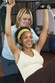 African woman exercising with personal trainer — Stock Photo