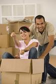 Man pushing wife in moving box — Stock Photo