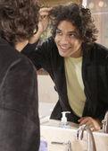 Hispanic man looking in bathroom mirror — Stock Photo
