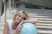 Young woman leaning on globe — Stock Photo
