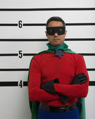 Male superhero standing in police line up — Stock Photo