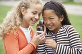Multi-ethnic girls listening to cell phone — Stock Photo