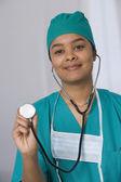 African female doctor holding up stethoscope — Stock Photo