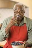 Senior African man eating fruit — Stockfoto