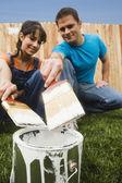 Multi-ethnic couple holding paintbrushes over can — Stock Photo