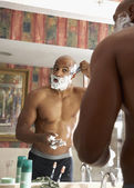 Mixed Race man shaving in bathroom — Stock Photo