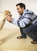 Mixed Race man playing with puppy dog — Stock Photo