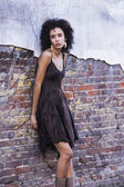 Mixed Race woman leaning against brick wall — Foto de Stock