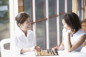 Asian mother and adult daughter playing chess — Stock Photo