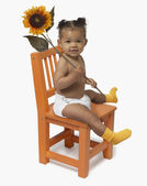 African American baby sitting chair with flower — Stock Photo