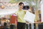 Mixed Race woman holding shopping bags — Stock Photo