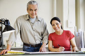 Hispanic male and female architects with blueprints — Stock Photo