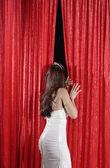 Hispanic beauty queen peeking through curtains — Stock Photo