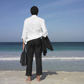 Hispanic businessman standing on beach — Stock Photo