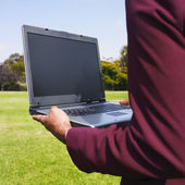 African businesswoman holding laptop in field — Stock Photo