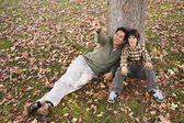 Mixed Race father and son pointing in park — Stock Photo