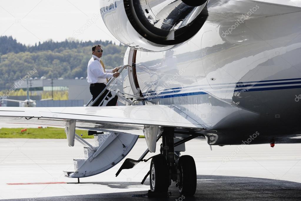 亚洲男性飞行员成私人飞机走楼梯