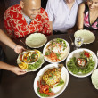 Multi-ethnic friends looking at table full of food — Stock Photo
