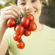 Asian woman holding tomatoes — Stock Photo