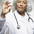 Stock Photo: Senior Hispanic female doctor holding medication