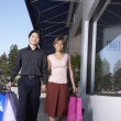 Asian couple carrying shopping bags — Stock Photo