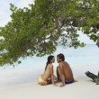 South American couple sitting on beach — Stock Photo