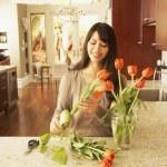 Hispanic woman cutting flowers — Stock Photo