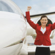 Businesswoman cheering next to airplane — Stock Photo