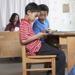 Multi-ethnic boys looking at cell phone in class — Stok fotoğraf