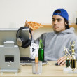 Mixed Race man eating pizza at computer desk — Stock Photo