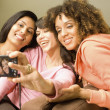 Multi-ethnic women taking own photograph — Stock Photo