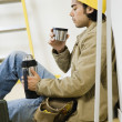 Mixed Race male construction worker drinking coffee — Stock Photo #23306358