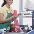 Mixed Race female grocery clerk ringing up items — Stock Photo #23306362