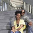 African couple sitting on stairs — Stock Photo
