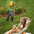 Gardener looking at Hispanic woman sunbathing — Stockfoto