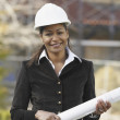 African American businesswoman holding blueprints - Stock Photo