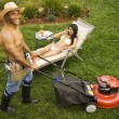 Stock Photo: Mmowing lawn while womsunbathes