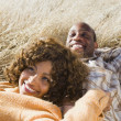 Stock Photo: AfricAmericcouple laying in field