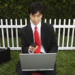 Asian businessman working inside fence — Stock Photo