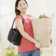 Asian woman carrying grocery bag — Stockfoto