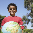Mixed Race boy holding globe — Stock Photo