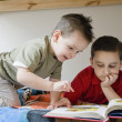 Hispanic brothers reading book — Stock Photo