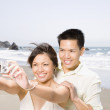 Asian couple taking own photograph at beach — Stock Photo