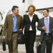 : Multi-ethnic businesspeople walking away from airplane — Stock Photo
