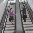 Hispanic businesspeople on escalators — Zdjęcie stockowe