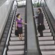 Hispanic businesspeople on escalators — Stock Photo #23307226